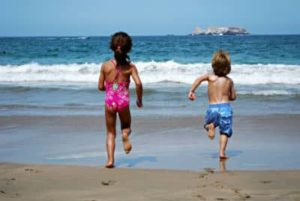 Two children are running towards the water on the beach and having fun