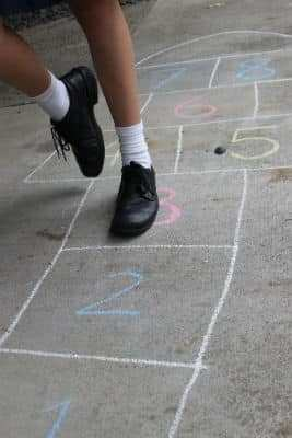 A girl is playing hopscotch drawn in chalk on the pavement