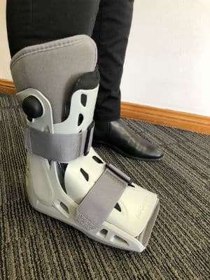 A person stands in a moon boot which can be used to treat lower limb stress fractures