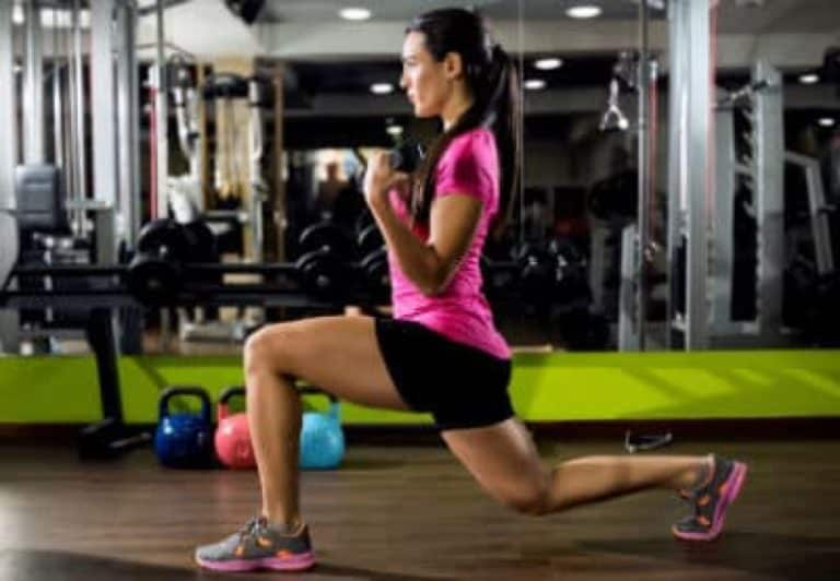 A woman working in a gym doing a lunge