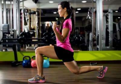 A young woman is performing a lunge whilst carrying a weight in a gym