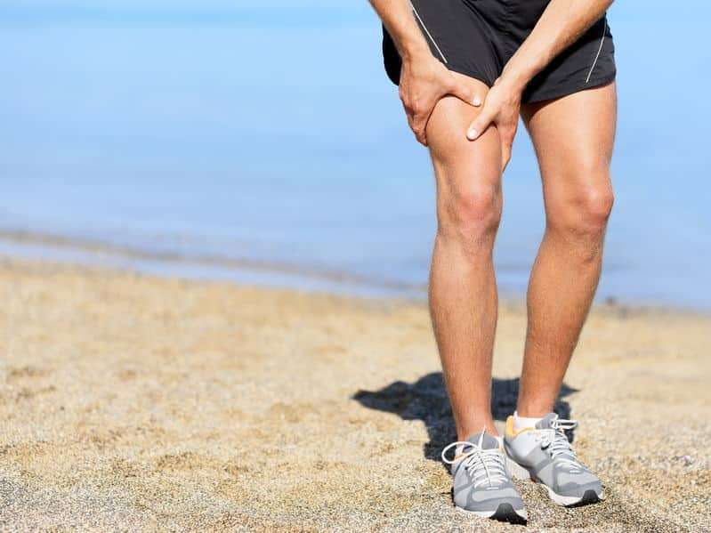 A man clutches his right thigh on the beach