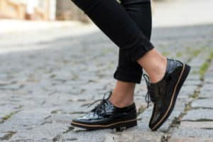 A pair of stylish black shoes on a lady