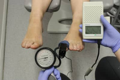 A podiatrist is performing a test of a patient's blood flow
