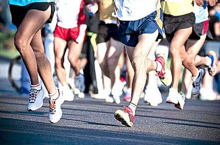 The bottom half of the bodies of runners in a marathon