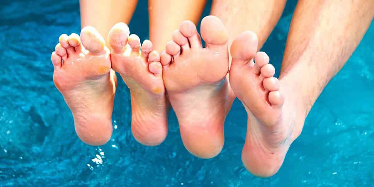 2 pairs of feet showing their toes over water