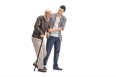 An elderly man with a cane is assisted walking by a young man.