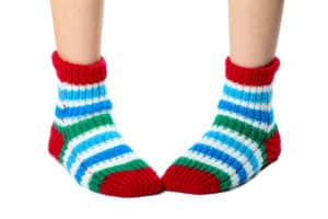 A pair of feet wearing brightly covered socks standing intoed
