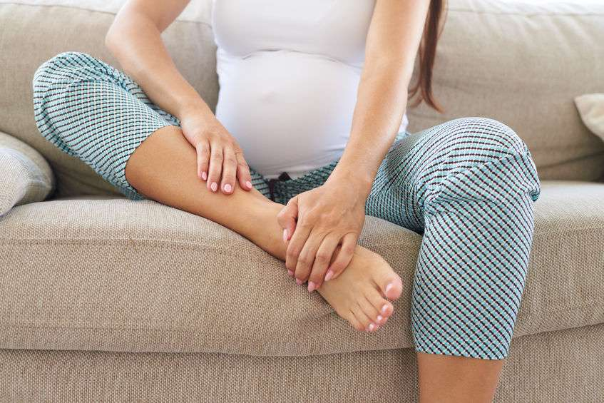 A pregnant lady massages her swollen feet and ankles on a sofa