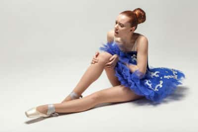 An injured ballet dancer holding her knee