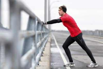 A man stretches his calf muscles on a bridge to prevent heel pain.