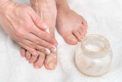 A Lady applies cream to her feet
